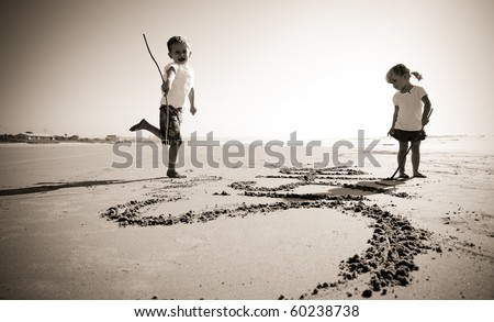 Lovely young brother and sister write words in the sand together