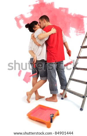 Lovely young couple of workers kissing against painting a wall