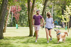 Lovely young couple running in the park with their dog during summer