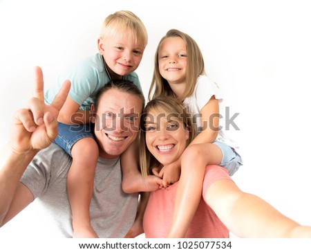 lovely young couple taking selfie photo self portrait with mobile phone carrying son and daughter on shoulders posing happy smiling isolated on white in family lifestyle concept