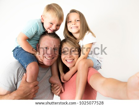 lovely young couple taking selfie photo self portrait with stick and mobile phone carrying son and daughter on shoulders posing happy smiling isolated on white in family lifestyle concept