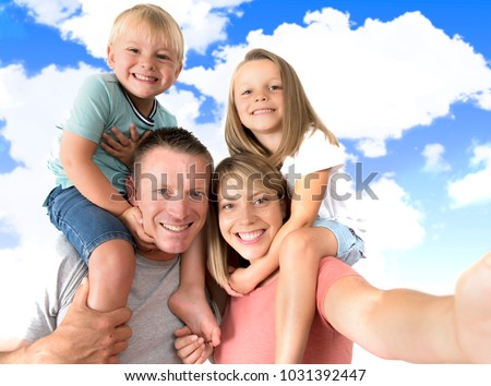 lovely young couple taking selfie photo self portrait with stick and mobile phone carrying son and daughter on shoulders posing happy smiling isolated on blue sky in family lifestyle concept