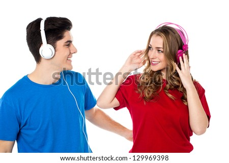 Lovely young couple with headphones on tuned into musical world.
