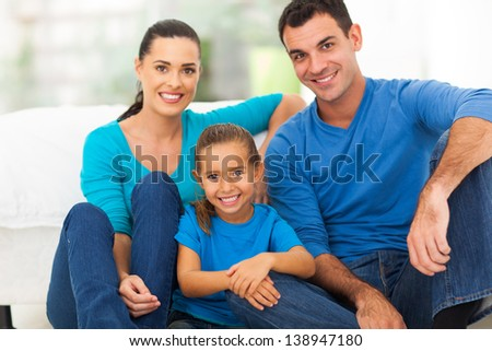 lovely young family of three sitting at home