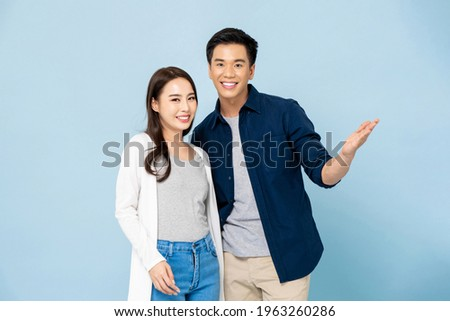 Lovely young happy smiling Asian couple in casual clothes on light blue isolated studio background