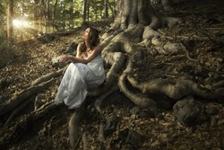 Lovely young lady wearing elegant white dress enjoying the beams of celestial light on her face sitting on the mighty roots of an ancient tree in enchanted woods