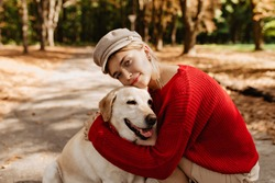 Lovely young woman in nice light hat and red sweater sitting with labrador together in the autumn park. Pretty blonde and her dog sitting among fallen leaves.