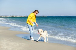 Lovely young woman walking the dog on a beach at synny day