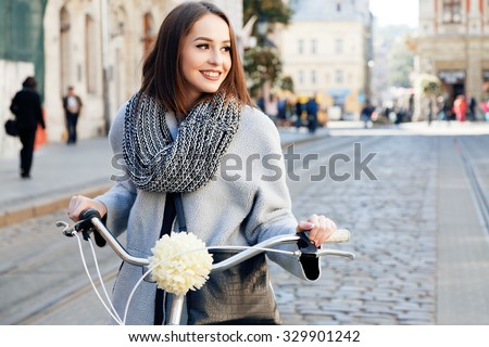 Lovely young woman, wearing in gray jacket and scarf, with black bag, posing with bike on the street of old European city, on sunny day, waist up #329901242