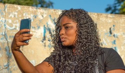Lovely young woman with long curly hair posing for selfie, by social network post. Candid outdoor caption. Connected world and inclusive beauty concepts