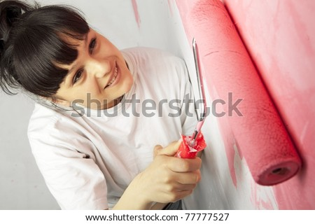 Lovely young worker painting a wall with roller