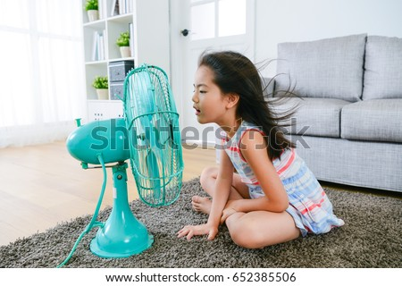 lovely youth little girl sitting on living room floor playing electric fan and enjoying cool wind in summer season at home. #652385506