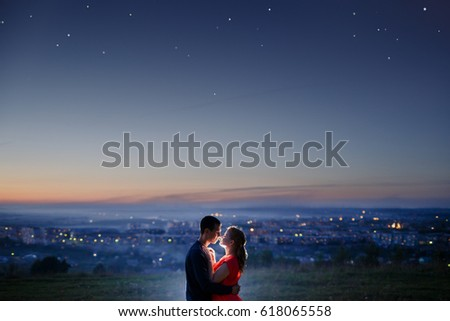 Lovers against background of night city, starry sky and horizon. Concept is date on roof, first love