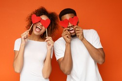Lovers blinded by their big love.. Young cheerful african-american couple in love holding red hearts over eyes and smiling, orange background