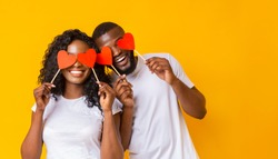 Lovers blinded by their big love.. Young cheerful african-american couple in love holding red hearts over eyes and smiling, yellow background, empty space