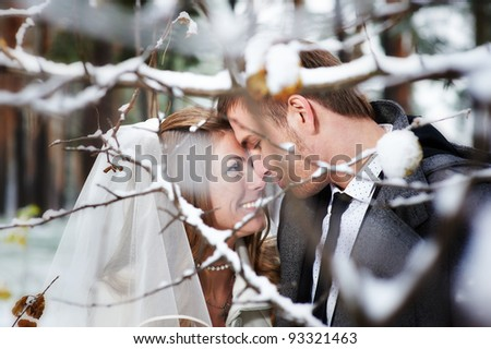 Lovers bride and groom look at each other in winter day