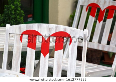 Lovers Cafe. White seats with red heart in cafeteria in street cafe. Two white wooden chairs on outdoor terrace in street restaurant. Chairs have painted hearts. Falling in love and romance concept.