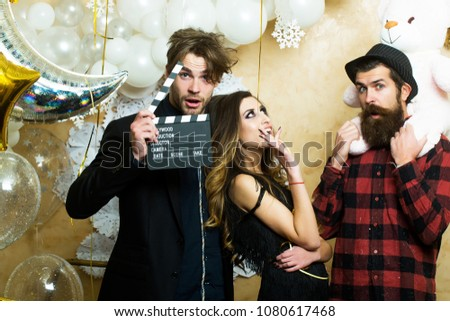 Lovers celebrate christmas or new year, love triangle. Boyfriends with movie clapper and teddy bear toy. Sensual woman and men in movie or film studio. Cinema theme party for holiday celebration.