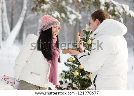 lovers give gifts in the wood near the decorated tree