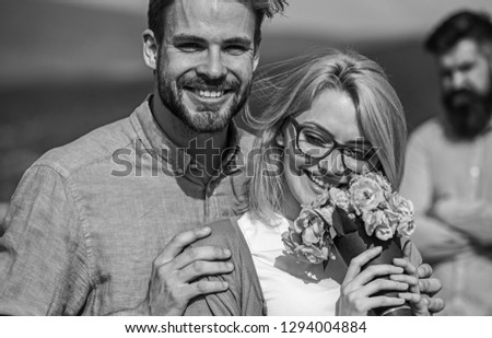 Lovers hugs outdoor flirt romance relations. Couple in love dating while jealous bearded man watching wife cheating him with lover. Infidelity concept. Couple romantic date lovers bouquet flowers. #1294004884