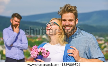 Lovers hugs outdoor flirt romance relations. Couple romantic date lovers bouquet flowers. Infidelity concept. Couple in love dating while jealous bearded man watching wife cheating him with lover. #1339809521