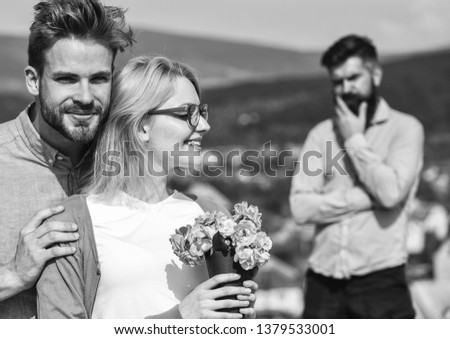 Lovers hugs outdoor flirt romance relations. Couple romantic date lovers bouquet flowers. Couple in love dating while jealous bearded man watching wife cheating him with lover. Infidelity concept. #1379533001