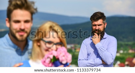 Lovers hugs outdoor flirt romance relations. Infidelity concept. Couple romantic date lovers bouquet flowers. Couple in love dating while jealous bearded man watching wife cheating him with lover. #1133379734