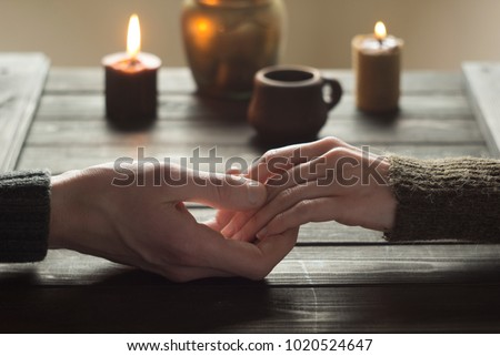 Lovers in a romantic table holding hands. Valentine's Day. A woman and a man spend candles in the evening together.