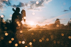 Lovers in the rain. The guy hugs the girl. Raindrops against the sunset background.
