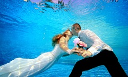 Lovers man and woman in wedding dresses kissing underwater in the pool and holding flowers in his hand. Horizontal orientation. A view from under the water from the bottom of the pool