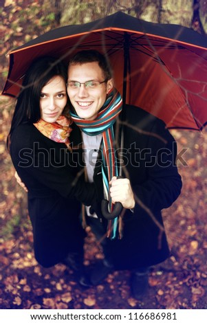 Lovers man and woman under an umbrella in the autumn forest