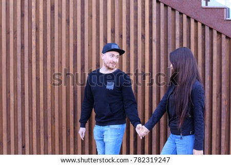 Lovers of heart walk past restaurant and going to go to dinner, holding hands and talking, share secrets and jokes, decide where to go to have fun. Guy dressed in black sweater, blue jeans, sneakers #782319247