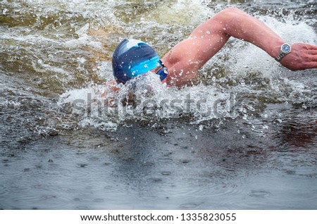Lovers of winter swimming.Swimmer swims in the pool.He swims the distance at speed. #1335823055