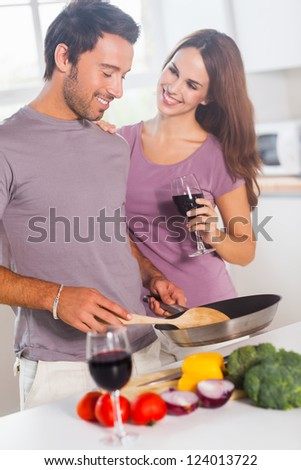 Lovers preparing food and drinking in kitchen