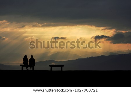 Lovers sit together on a bench by the dam in the morning to watch the sunrise in the morning of the bright winter and talk about the love that has always been there. Concept of Love and Commitment Stock fotó ©