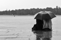 lovers sitting on quay in rain