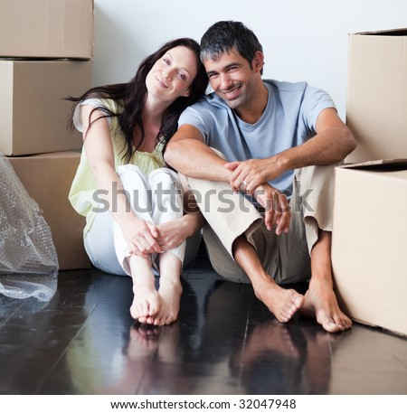 Lovers sitting on the floor of their new house