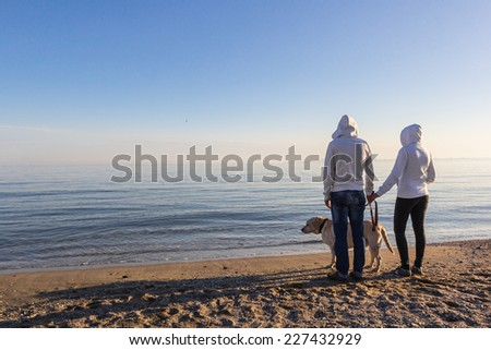 Lovers walk along the shore of a tropical beach with a dog