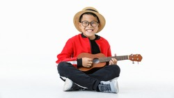 Lovey cutout portrait of young Asian healthy boy wearing brown hat, glasses, red shirt, and long black pants happily sitting with smile while enjoy performing as musician by playing small guitar