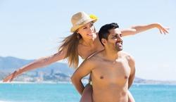 Loving adult couple having fun at seashore at sunny day