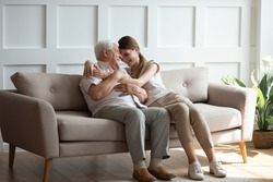 Loving adult grown up granddaughter hug old grandfather sitting on sofa in sunny living room, different generations woman and man relative people understanding connection care sincere feelings concept