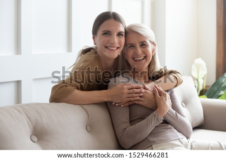 Loving adult 30s daughter hug elderly mother from behind while mom sitting on couch people posing looking at camera smiling feels happy, concept of multi generational family, relative devoted person