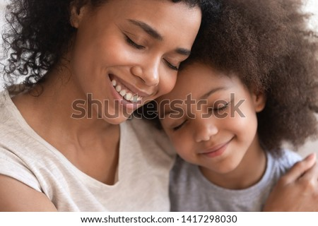 Loving affectionate family young african american mother holding embracing cute little kid daughter, happy black mom foster parent hug small mixed race child cuddling and bonding with eyes closed
