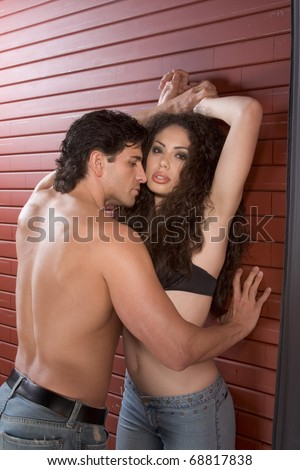 Loving affectionate nude heterosexual couple in affectionate sensual kiss. Mid adult Caucasian men in late 30s and young Latina woman in early 20s