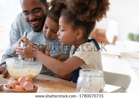 Loving african american father make dough making tasty sweet breakfast pastry with excited little children, happy biracial dad and small kids cook prepare pancakes cookies pie in kitchen together