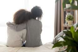 Loving african american single mother sister embrace teen daughter sit on bed looking at window, parent mom hug support protect teenage girl, family trust hope talk understanding concept, rear view