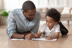 Loving african american smiling father in eyeglasses helping or learning little cute curly son drawing or coloring picture. Happy family lying on wooden warm heated floor, creative art activity.