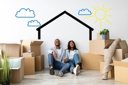 Loving african american spouses relocating to their own home, dreaming about renovation while sitting near white wall with drawn house among cardboard boxes