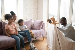 Loving african American young dad make in puppet show to excited young wife sit relax on couch with little kids, happy biracial family have fun entertain in cozy living room, watch theater play