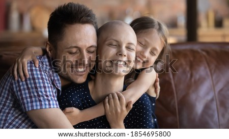 Photo of  Loving and caring. Affectionate happy young husband dad and school age daughter kid sitting on couch supporting cuddling warm tight beloved smiling millennial wife mom fighting against cancer disease